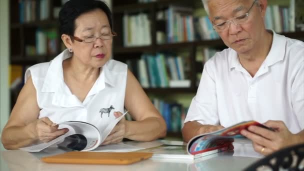 Asian senior couple reading books and magazines together in small library. Learning and study concept
