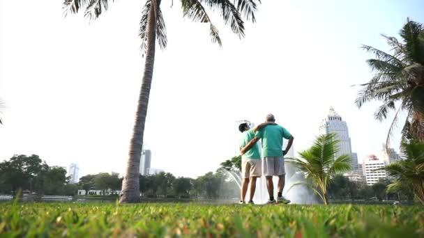 Videó az ázsiai vezető idős pár gyakorlat szabadtéri tó és a városi park háttérrel. Absztrakt szerelem egészség és természet