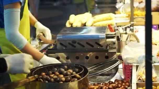 Prodávající grilování chobotnice a loupání pečené kaštany na pouličních stánků. Podzimní jídlo z Asie