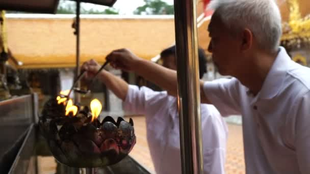 Asian senior doing Buddhist ritual pouring oil to fill candle frame for BUddha statue