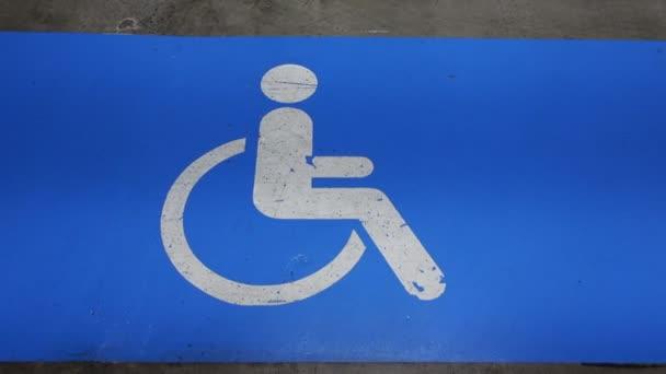 Blaues Handicap-Schild auf Parkplatz mit Sonderreservefläche beschmiert