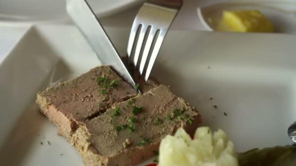 Nůž a vidlička krájení paštiky husí játra předkrm ve francouzské restauraci s nakládanými okurkami a bramborovou kaší