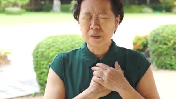 Senior donna asiatica che ha attacco di cuore, dolore toracico