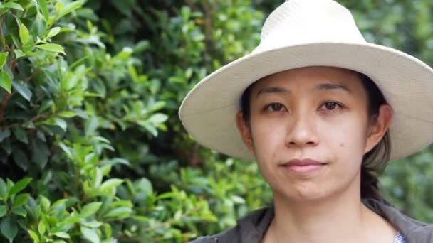 Video of Beautiful smiling Asian woman closeup portrait. Wearing hat with natural green bush background. modern life condominium