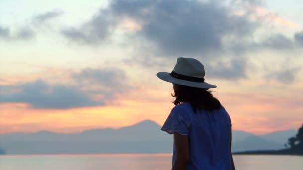 Videó az ázsiai nő sziluett, élvezi Seascape kalap alatt napkelte. gyönyörű trópusi strandok és a táj
