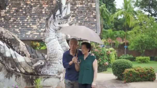 Video z asijských starší pár pod deštníkem v dešti v chrámu