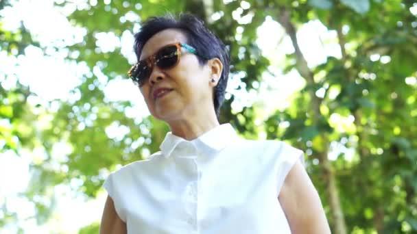 Cool asijských starší žena nosí sluneční brýle v zelené přirozeného pozadí na bílou košili