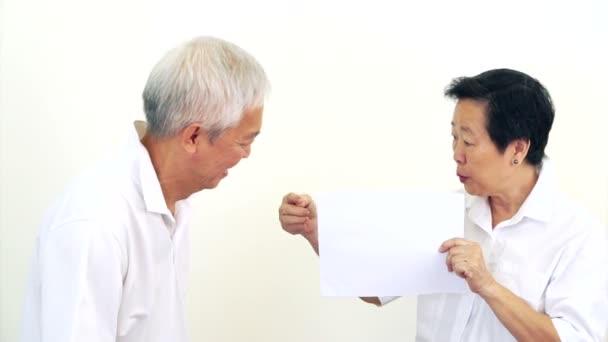 Video z asijských starší pár společně podívat na bílou cedulí. Překvapení a radost s dohodu o prázdné bílé znamení