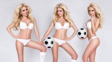 Beautiful young athletic girl blonde woman dressed in sports attire holding and playing football and joyfully smiles