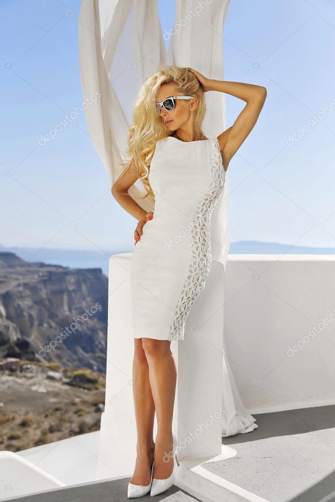 Sehr schöne langhaarige blonde stehende Frau in sexy weißes kurzes ...