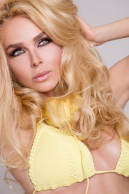 Portrait of a very beautiful blond hair woman in sexy yellow dress with yellow headphones around his neck in a wondrous makeup