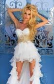 krásná blonďatá nevěsta v bílé svatební šaty s báječné velmi dlouhý vlak krystalů je sexy na schodech opřený modré brány v ulici na santorini v Řecku
