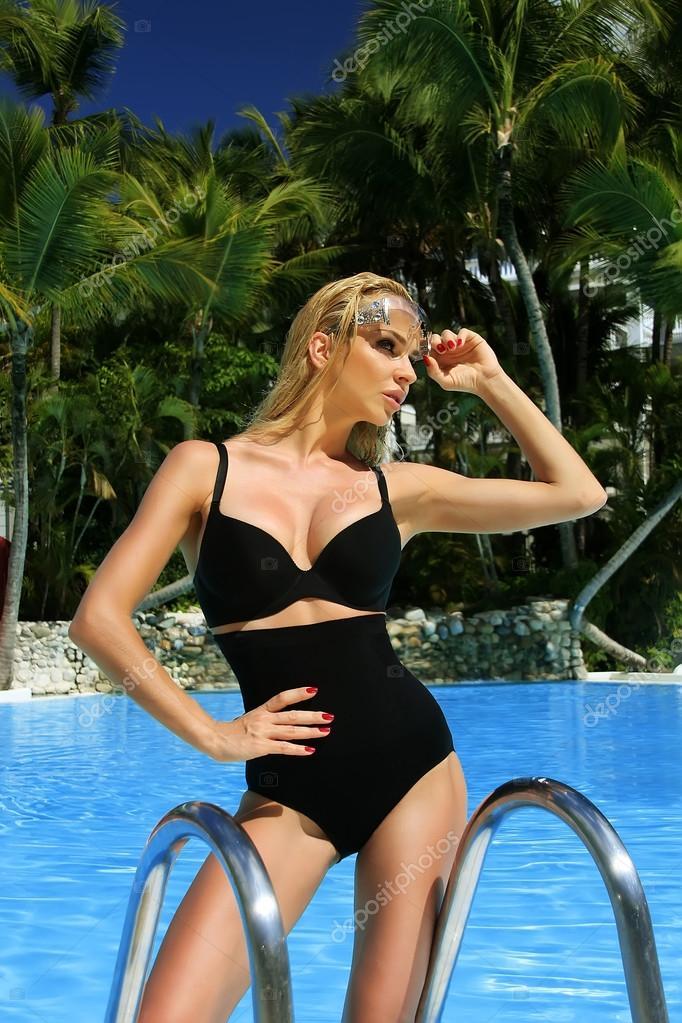 Velmi krásné sexy blond dlouhé vlasy-žena stojí v sexy černé plavky na  krásném bazénu v okolních neobvyklé divoké a exotické flóry — Fotografie od  ... 7eec0d8387