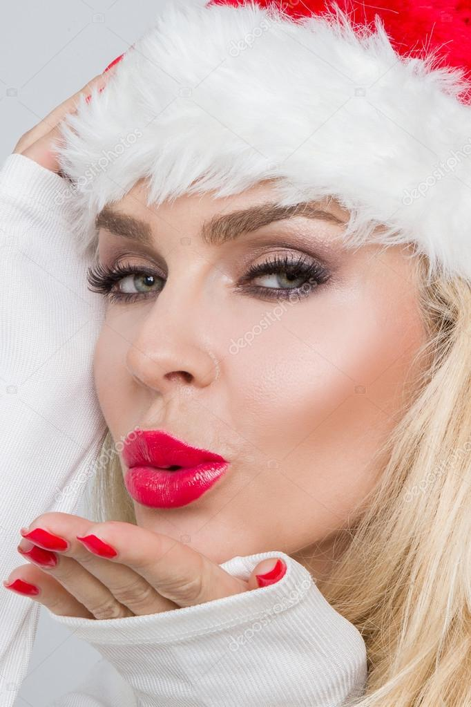 Beautiful sexy blonde female model dressed as Santa Claus in a red cap with a tassel at the White fur lovely makeup sensual lips, beauty photo Christmassy, Christmas