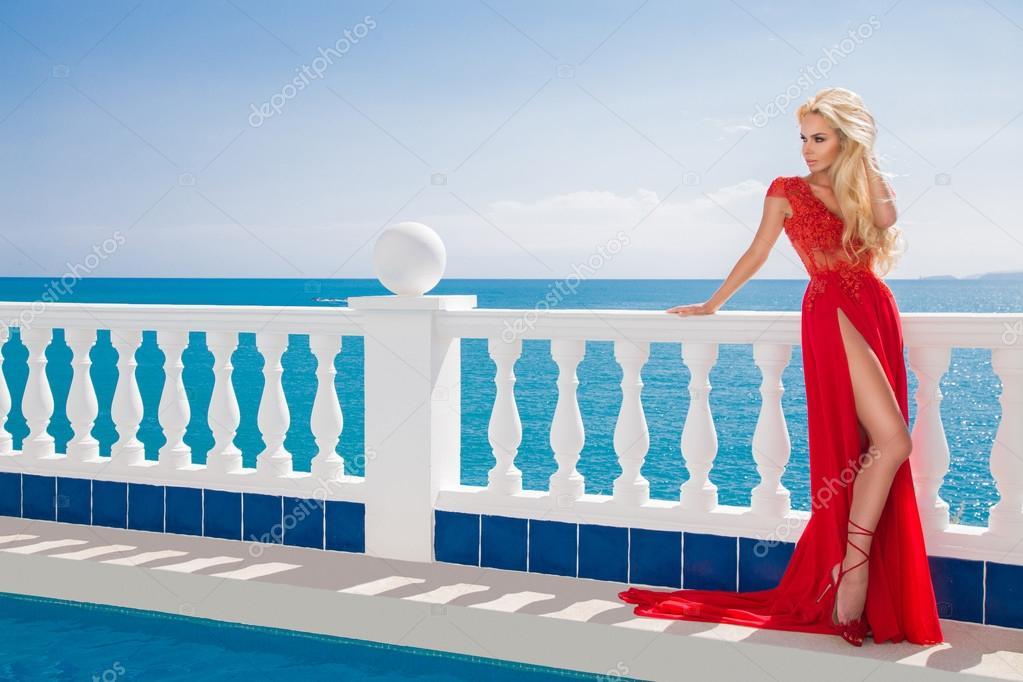 Roztomilý blond vlasy sexy modelka dívka v modrém fondu v červené elegantní dlouhé  šaty s dlouhým vlak s pozadím krystaly modré moře v Santorini– stock ... 47078620b6