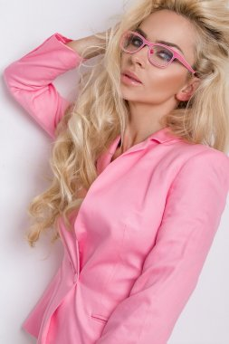 beautiful lush blond curly hair sexy model with green eyes in glasses in the pink elegant jacket, suit and white pants on a white background