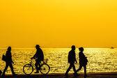 Silhouetten von Menschen, die einen Spaziergang am Meer der Stadt genießen