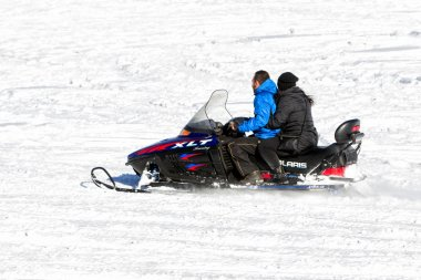 Visitors enjoy the snow on snowmobiles in Falakro ski center, Gr