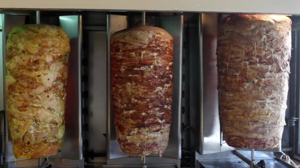 A pair of rotating skewered chicken and lamb meat grilled and ready to serve in a typical Middle Eastern sandwich