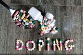 Slovo doping napsal s prášky na dřevěné pozadí