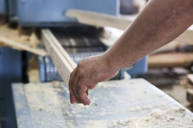 Craftsmen cut a piece of wood at a woodworking factory in Greece