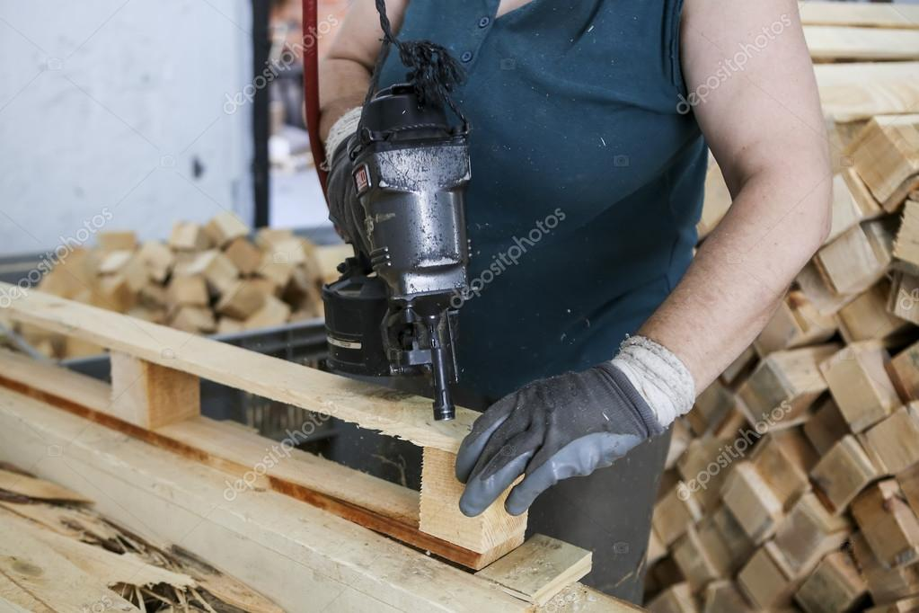Craftsman Puts Nails In A Piece Of Wood At A Woodworking Factory