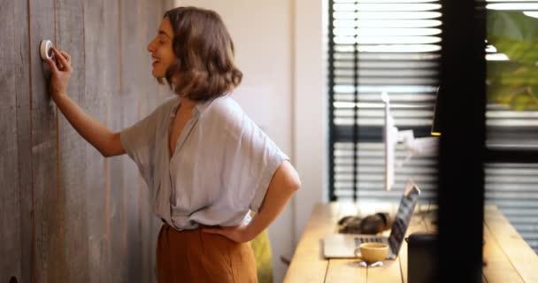 Frau kontrolliert Temperatur zu Hause mit Thermostat