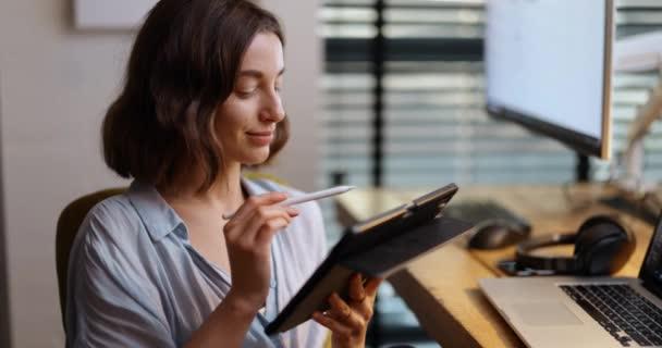 Žena pracující na digitálním tabletu v domácí kanceláři