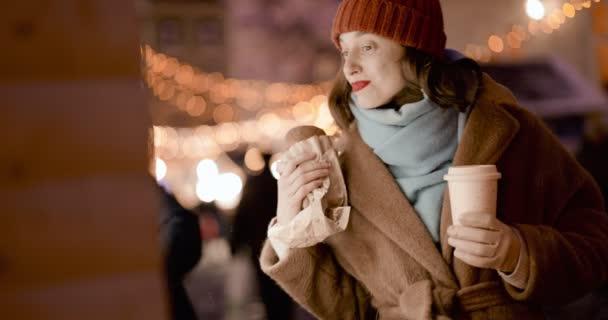 Woman with food at Christmas market at night