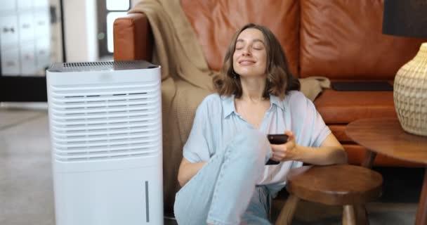 Frau mit Luftreiniger oder Klimaanlage zu Hause