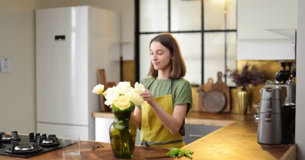 Woman decorates home interior with a bouquet of fresh flowers