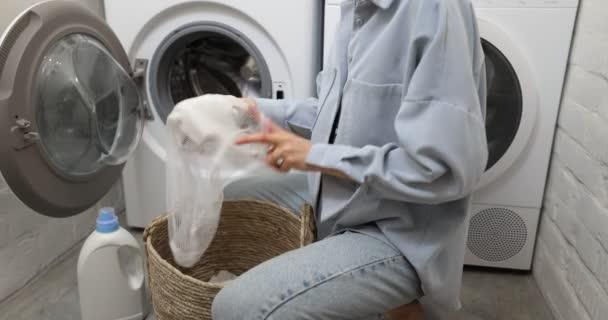 A nő ruhákat tesz a szennyes zsákba.