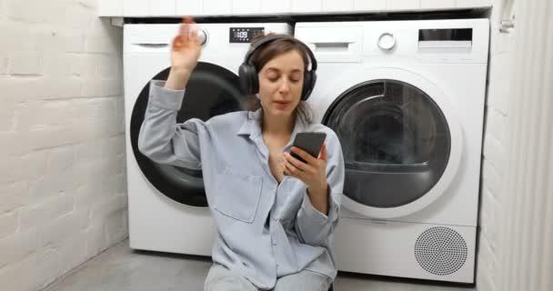 Frau genießt beim Wäschewaschen zu Hause