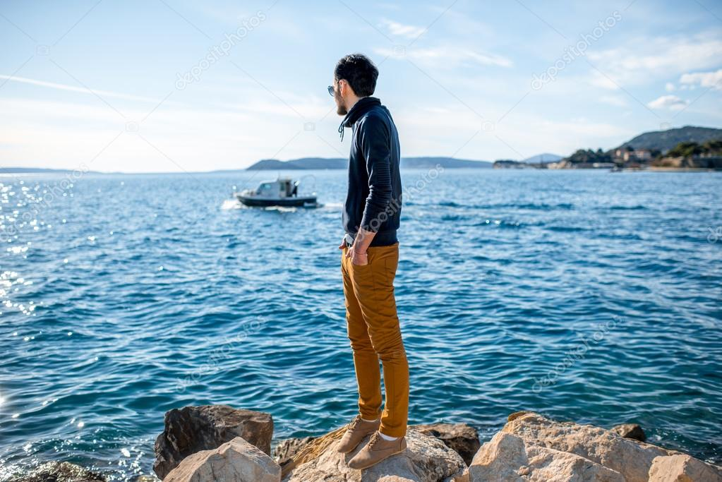 Man watching boat on the sea