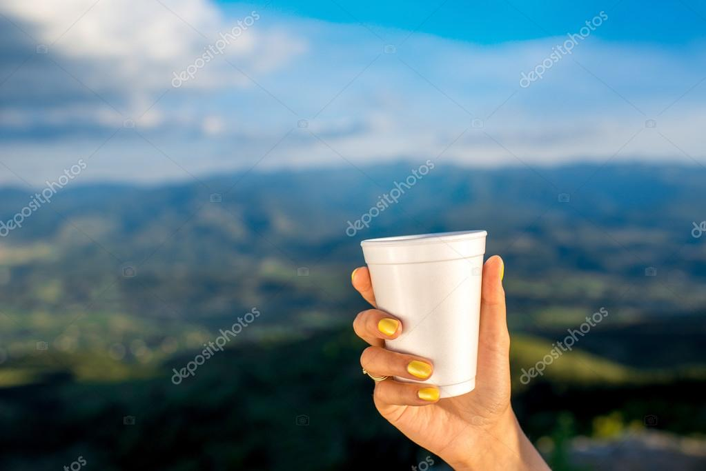 Holding white paper coffee cup