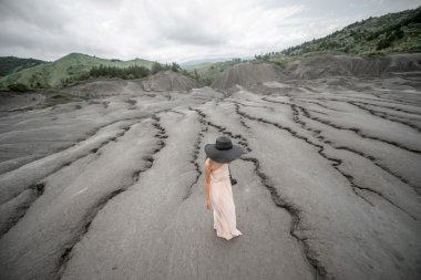 Female traveler near mud volcanoes