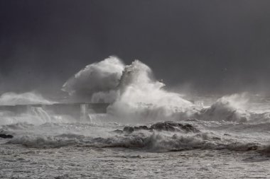 Stormy waves over old lighthouse and pier