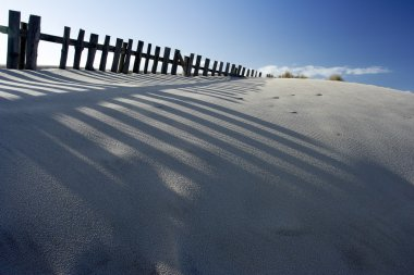 Sand dune with fences and shadows