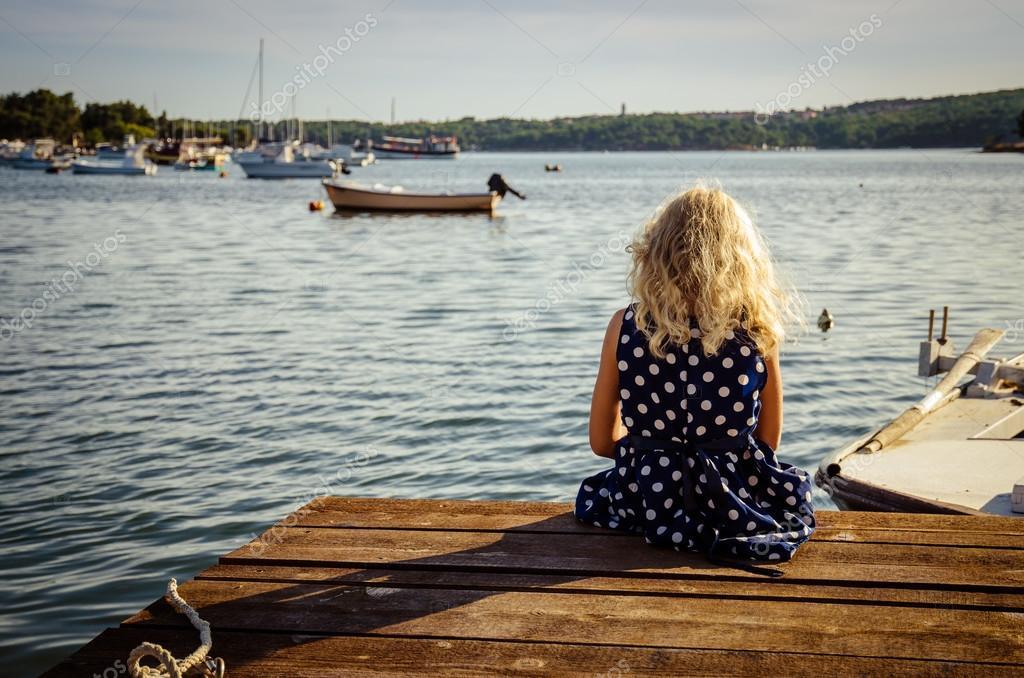girl sitting in wooden jetty