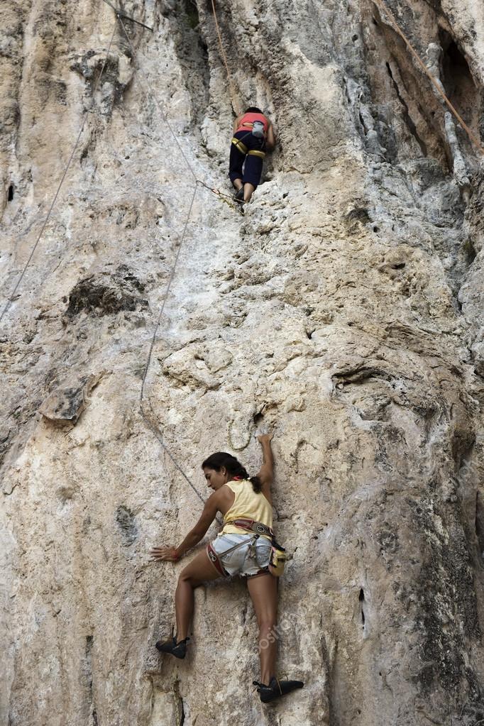 Rock climbers climbing the wall on Phra Nang beach