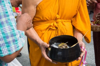 Buddhist monks are given food offering from people for End of Buddhist Lent Day