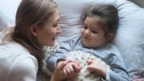 Adorable mother speaking with her cute preschooler little kid girl telling a fairy tail, holding hands, smiling and lying on the bed.