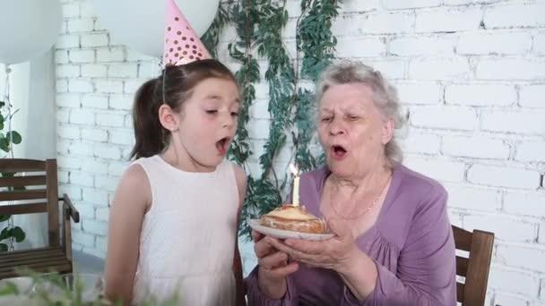 Lassú mozgás. Boldog mosolygós kislány és idősebb nagymama ünnepli 85. születésnapját, tartja torta és elfújja gyertyát együtt, fehér tégla háttér. Élvezze, tisztelet és meleg kapcsolat koncepció