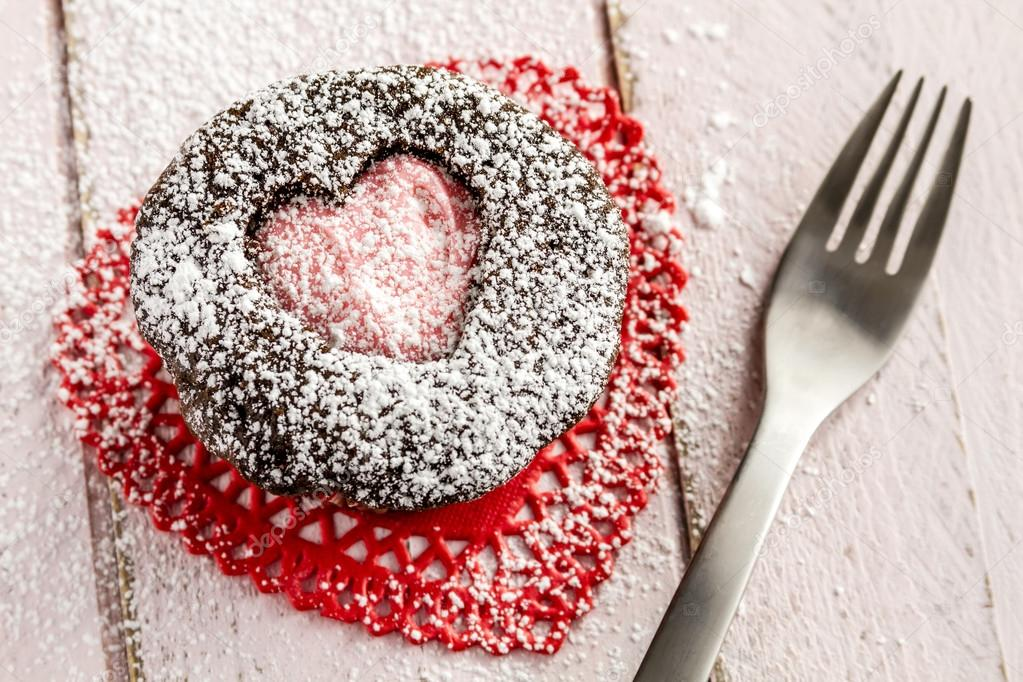 Chocolate cupcake with heart shaped cutout on top filled with pink frosting sitting on red lace doily with a fork dusted with powdered sugar