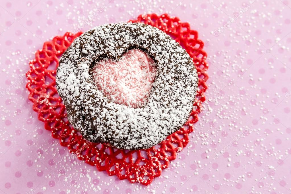 Chocolate cupcake with heart shaped cutout on top filled with pink frosting sitting on red lace doily on pink polka background dusted with powdered sugar