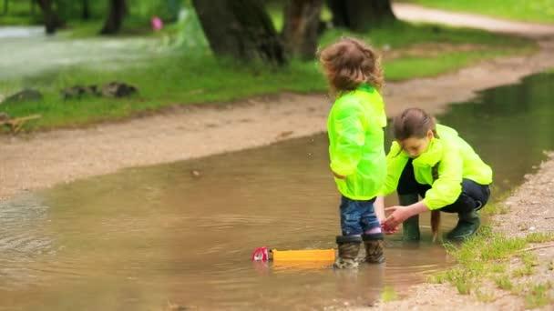 entzückende Kinder spielen nach dem Regen in einer riesigen Pfütze
