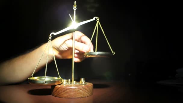 Man Placing Weights on Golden Balance Scales Standing On Table