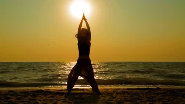 mladá žena cvičí jógu na pláži při západu slunce
