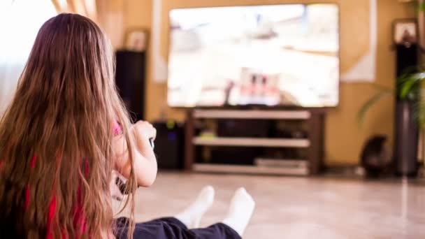 Egy lány ül a földön konzol játszik
