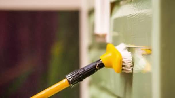 Person wäscht Hauswand mit Wasserstrahl und Pinsel